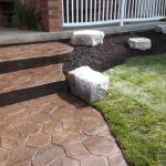 Stamped coloured concrete sidewalk with a new lawn and Armour Stone in the garden.