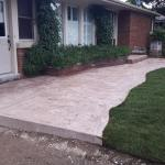 Coloured concrete sidwalk with new sod, and a lightpost on a concrete pad.