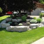 Armour Stone garden with river rock, mulch and shrubs in front yard.