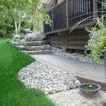 Finished Armour Stone retaining wall, sidewalk, and river rock landscaping.