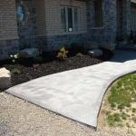 New Armour stone garden with black mulch next to a decorative concrete sidewalk.