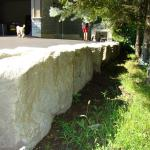 A solid Armour Stone wall supporting a driveway.