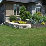 Armour stone edging around beautiful landscaped garden in front of this luxury home.