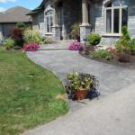 Grey stamped concrete sidwalk leading up to front door of house.