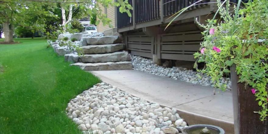 Armour stone retaining wall with stone steps and new concrete sidewalk with river rock.