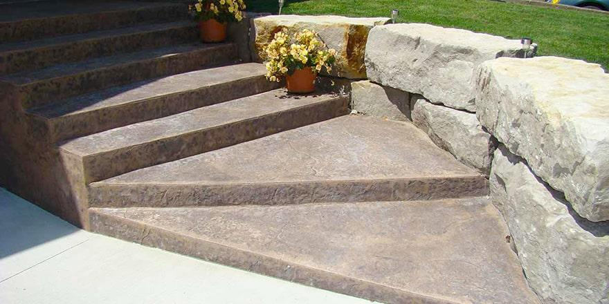 Stamped decorative coloured concrete with Armour stone retaining wall.