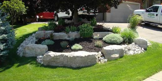 Armour stone garden with river rock and shrubs.