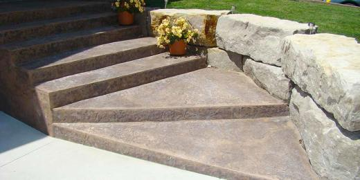 Stamped concrete steps with armour stone retaining wall.